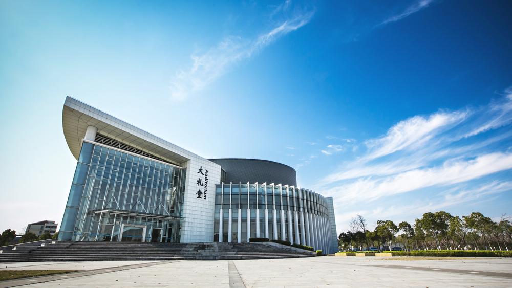 上海海事大学大礼堂位于临港校区北区,处于由体育馆、中心湖面形成的南北轴线上,总建筑面积5003平方米,设观众席座988座和一个200平方米的排练厅,建筑的整体灵感来源于鹦鹉螺的壳体形式,这一简单而又经典的海洋生物在地球上已持续存在几百万年,螺旋上升的绿色屋面冉冉升起,一座巧妙围合的椭圆形舞台,成为整个建筑的参观流线的中心焦点,象征着71%的地球表面以水覆盖,水面带来了水波的波纹、质感、动感、声音和反射。在立面形态上,考虑到学校与海在内涵和外延上的内在联系,设计中引入了水的概念,用竖向的建筑语言,