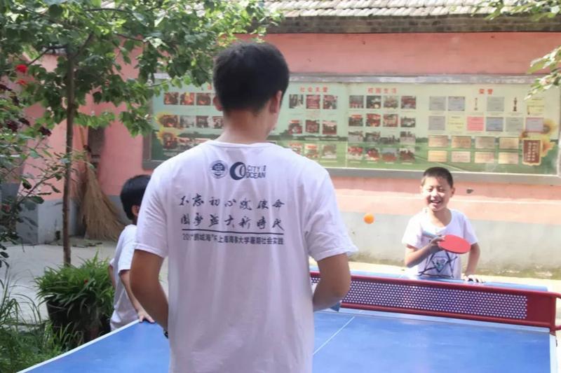 开心地跟老师打乒乓球的孩子