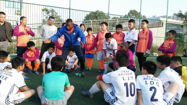 路易斯教中国孩子踢足球