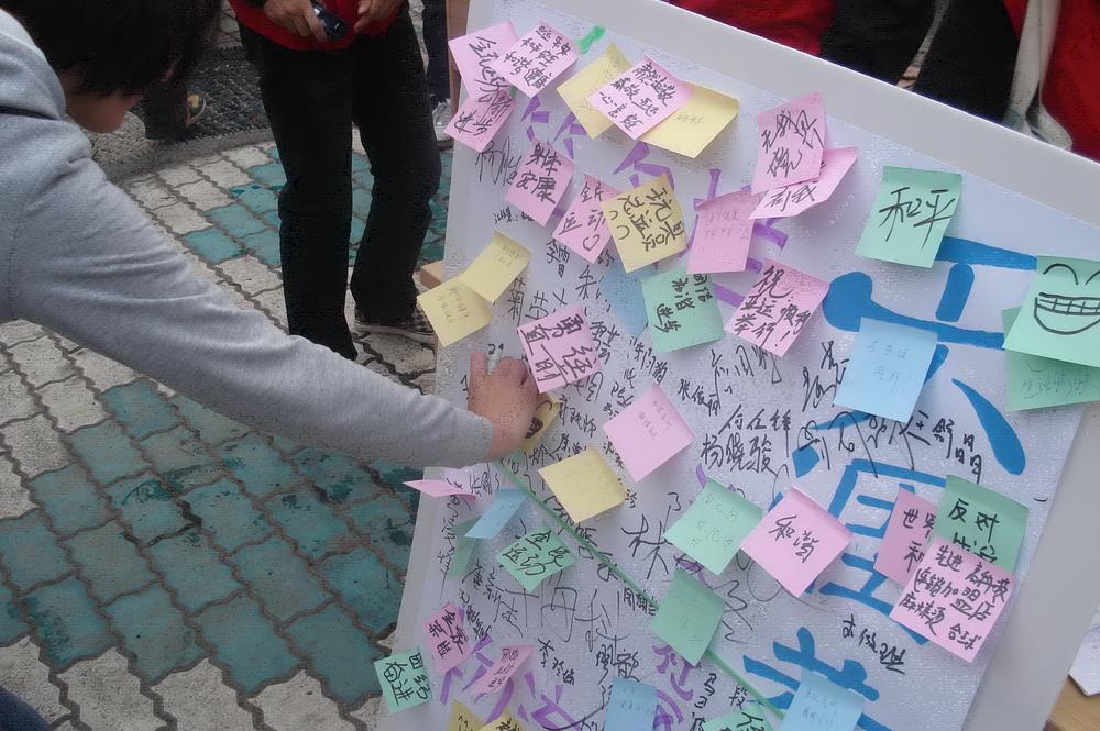 同学们与社区居民一起书写十八大寄语