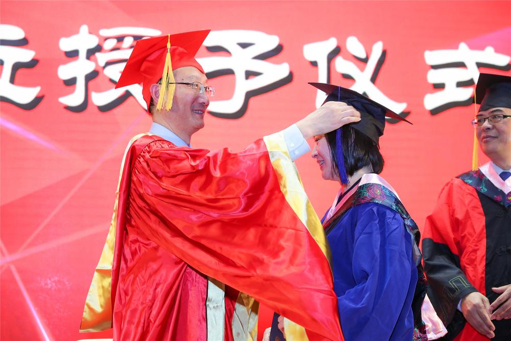 黄校长为毕业生拨苏正冠并授予学位证书