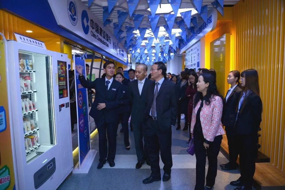 学生行长向嘉宾介绍校园e银行内各种智能设备