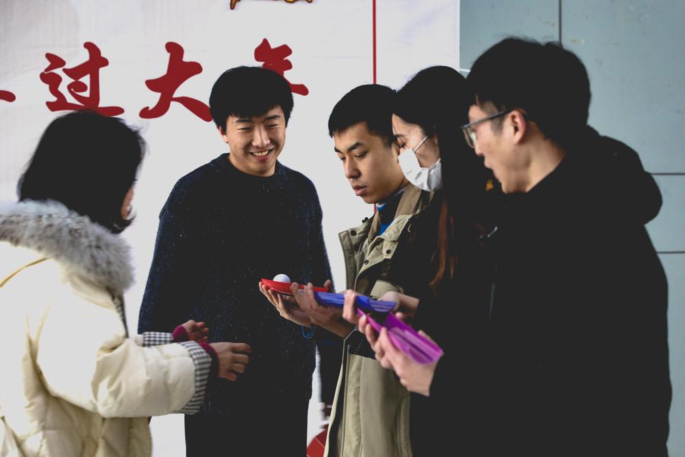 """学生参与迎春游园会同心协力""""幸运传递""""项目"""