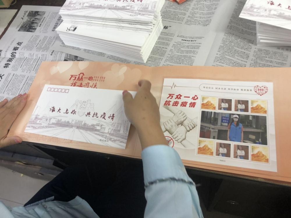 为参加志愿服务的教职工送上纪念册