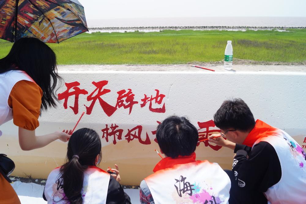 党员志愿者们仔细勾勒墙绘