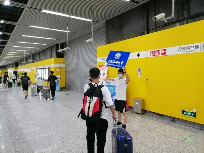志愿者在临港大道地铁站迎新